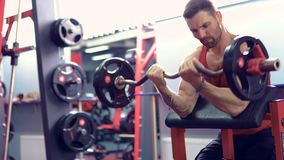 Άτομο bodybuilder που κάνει το σύνολο μιας άσκησης barbell σε μια γυμναστική Πραγματικός - χρονικός πυροβολισμός φιλμ μικρού μήκους
