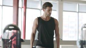 Άτομο bodybuilder που χρησιμοποιεί τους αλτήρες για lunges τη στάση οκλαδόν στην αθλητική κατάρτιση στην ικανότητα φιλμ μικρού μήκους
