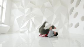 Άτομο Breakdancer που εκτελεί τις δροσερές κινήσεις χορού στο πάτωμα σε ένα άσπρο στούντιο απόθεμα βίντεο