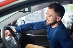 Άτομο Brunette με τη γενειάδα στην μπλε συνεδρίαση πουλόβερ στο νέο αυτοκίνητο στοκ φωτογραφία με δικαίωμα ελεύθερης χρήσης