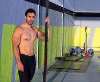 Άτομο Crossfit με την αναρρίχηση του σχοινιού που χαλαρώνουν στη γυμναστική Στοκ Εικόνες