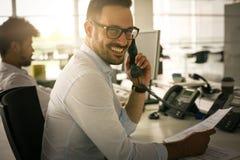 Άτομο Cusiness που έχει τη συνομιλία στο τηλέφωνο γραμμών εδάφους Bu Στοκ Εικόνα