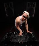 Άτομο DJ στην άσπρη μουσική παιχνιδιού πουκάμισων σε έναν αναμίκτη του DJ ` s όμορφες νεολαίες γυναικών στούντιο ζευγών χορεύοντα Στοκ Εικόνες