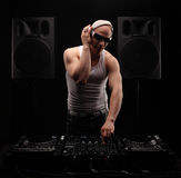 Άτομο DJ στην άσπρη μουσική παιχνιδιού πουκάμισων σε έναν αναμίκτη του DJ ` s όμορφες νεολαίες γυναικών στούντιο ζευγών χορεύοντα Στοκ εικόνα με δικαίωμα ελεύθερης χρήσης