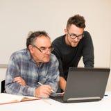 Άτομο eldery διδασκαλίας νεαρών άνδρων της χρήσης του υπολογιστή Intergenerat στοκ εικόνα