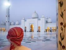 Άτομο Emarati που εξετάζει Sheikh το μεγάλο μουσουλμανικό τέμενος Zayed στο ηλιοβασίλεμα στο Αμπού Ντάμπι στοκ εικόνες με δικαίωμα ελεύθερης χρήσης