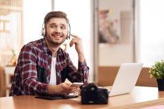 Άτομο Freelancer που ακούει τη μουσική στη συνεδρίαση lap-top στο γραφείο στοκ φωτογραφία με δικαίωμα ελεύθερης χρήσης