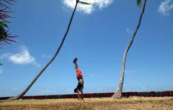 Άτομο Handstanding στη χλόη κατά μήκος της ακτής απότομων βράχων δίπλα σε ρηχό Στοκ Φωτογραφίες