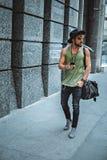 Άτομο Hipster που περπατά στην οδό κρατώντας το τηλέφωνό του Στοκ φωτογραφία με δικαίωμα ελεύθερης χρήσης