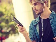 Άτομο Hipster που στέκεται στη μουσική ακούσματος οδών πόλεων Στοκ Φωτογραφία