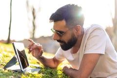 Άτομο Hipster που χρησιμοποιεί μια ψηφιακή ταμπλέτα σε ένα πάρκο στοκ φωτογραφία με δικαίωμα ελεύθερης χρήσης