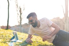 Άτομο Hipster που χρησιμοποιεί μια ψηφιακή ταμπλέτα σε ένα πάρκο στοκ φωτογραφία