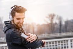 Άτομο Jogger με τα ακουστικά που χρησιμοποιούν τη μουσική Smartphone και ακούσματος Στοκ Φωτογραφίες