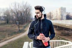 Άτομο Jogger με τα ακουστικά που χρησιμοποιούν τη μουσική Smartphone και ακούσματος Στοκ εικόνα με δικαίωμα ελεύθερης χρήσης