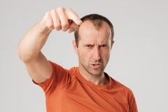 Άτομο Mture στο πορτοκαλί τ -τ-shirtfinger που δείχνει προς τη κάμερα σε ένα γκρίζο υπόβαθρο Στοκ εικόνες με δικαίωμα ελεύθερης χρήσης