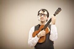 Άτομο Nerd με το παιχνίδι γυαλιών ukulele Στοκ φωτογραφία με δικαίωμα ελεύθερης χρήσης