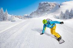 Άτομο snowboarder που οδηγά στην κλίση στοκ φωτογραφίες