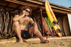Άτομο Surfer eyeglasses που κάθονται και που μιλούν στο smartphone υπαίθρια Στοκ Εικόνα