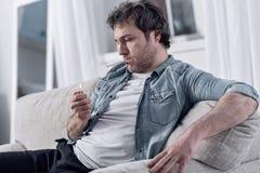 Άτυχη συνεδρίαση ατόμων στο σπίτι και φωτισμός ένα τσιγάρο Στοκ φωτογραφίες με δικαίωμα ελεύθερης χρήσης