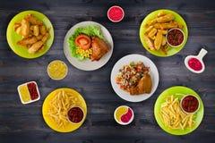 Άχρηστο φαγητό Γρήγορο φαγητό Τηγανιτές πατάτες, πόδι, σάλτσες στον πίνακα Στοκ Εικόνες