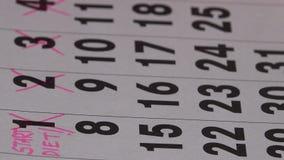 Δάχτυλα γυναικών με το ρόδινο δείκτη που διασχίζει τις ημέρες στο ημερολόγιο Έναρξη της έννοιας διατροφής απόθεμα βίντεο
