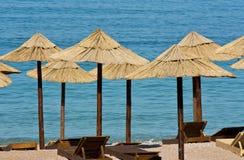 Άχυρο sunshades και ξύλινα sunbeds σε μια κενή παραλία Στοκ φωτογραφίες με δικαίωμα ελεύθερης χρήσης