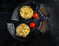 Άψητα ιταλικά ζυμαρικά Fettuccine σε ένα σπασμένο μαύρο πιάτο με τις ντομάτες κερασιών στοκ εικόνα με δικαίωμα ελεύθερης χρήσης