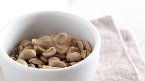 Άψητα πράσινα ακατέργαστα φασόλια καφέ που εμπίπτουν στο πιάτο φιλμ μικρού μήκους