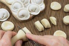 Άψητες μπουλέττες Τα χέρια κόβουν τη ζύμη στα κομμάτια Στοκ φωτογραφία με δικαίωμα ελεύθερης χρήσης