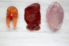 Άψητη ακατέργαστη μπριζόλα σολομών, κρέας βόειου κρέατος και στήθος της Τουρκίας στο άσπρο ξύλινο υπόβαθρο, τοπ άποψη Επίπεδος βά Στοκ φωτογραφία με δικαίωμα ελεύθερης χρήσης