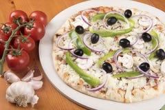 Άψητη χορτοφάγος πίτσα με τις ελιές, τα πιπέρια, το κρεμμύδι, τα μανιτάρια και το σκόρδο στοκ εικόνες