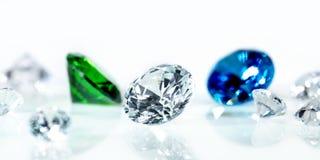 Άψογα διαμάντια, μπλε σάπφειρος και μια πράσινη σμάραγδος μπροστά από το άσπρο υπόβαθρο στοκ εικόνες με δικαίωμα ελεύθερης χρήσης