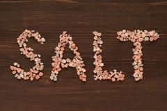 Άλας λέξης που γράφεται στα ρόδινα αλατισμένα κρύσταλλα Hymalayan Στοκ εικόνα με δικαίωμα ελεύθερης χρήσης
