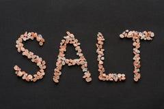 Άλας λέξης που γράφεται στα ρόδινα αλατισμένα κρύσταλλα Hymalayan Στοκ Εικόνα