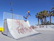 Άλματα αγοριών με το μηχανικό δίκυκλό του πέρα από μια κεκλιμένη ράμπα σε ένα skatepark Στοκ φωτογραφία με δικαίωμα ελεύθερης χρήσης