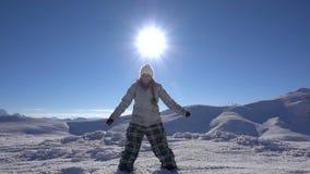 Άλματα κοριτσιών snowboarder επάνω στην κορυφή βουνών απόθεμα βίντεο