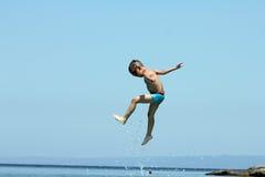 Άλματα μικρών παιδιών στη θάλασσα Στοκ Εικόνες
