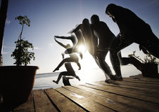 Άλμα αγοριών στη θάλασσα από την πλατφόρμα στη σειρά το βράδυ Στοκ φωτογραφία με δικαίωμα ελεύθερης χρήσης