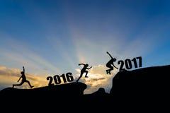 Άλμα ατόμων μεταξύ 2016 και 2017 έτη στο υπόβαθρο ηλιοβασιλέματος Στοκ Εικόνες