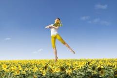 Άλμα κοριτσιών πέρα από τα κίτρινα λουλούδια Στοκ εικόνα με δικαίωμα ελεύθερης χρήσης