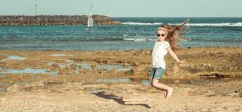 Άλμα μικρών κοριτσιών σε μια παραλία Στοκ φωτογραφία με δικαίωμα ελεύθερης χρήσης