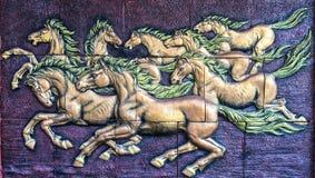 Άλογα αγαλμάτων που τρέχουν σε ένα κόκκινο υπόβαθρο Στοκ Εικόνες