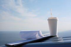 Έγγραφα και φλιτζάνι του καφέ στο αυτοκίνητο κουκουλών Στοκ εικόνα με δικαίωμα ελεύθερης χρήσης