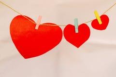 Έγγραφα μορφής καρδιών που κρεμούν στη γραμμή υφασμάτων με τις καρφίτσες υφασμάτων Στοκ Φωτογραφίες