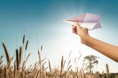 Έγγραφο αεροπλάνων στο χέρι παιδιών, μέση στο λιβάδι και μπλε ουρανός Στοκ Φωτογραφίες