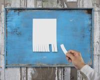 Έγγραφο δακρυ'ων χεριών από την κενή διαφήμιση που ταχυδρομείται ξύλινο σε billboar στοκ φωτογραφία