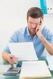 Έγγραφο ανάγνωσης επιχειρηματιών στο γραφείο του στο γραφείο του Στοκ εικόνες με δικαίωμα ελεύθερης χρήσης