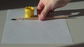 Έγγραφο, βούρτσα και ένα βάζο του κίτρινου ακρυλικού χρώματος γκουας στο TA φιλμ μικρού μήκους
