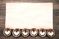 Έγγραφο για το ξύλινο υπόβαθρο με τις αφηρημένες καρδιές Στοκ Εικόνες