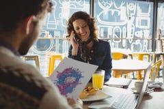 Έγγραφο εκμετάλλευσης ανδρών με τη ζωγραφική από τη γυναίκα στον καφέ Στοκ Εικόνες